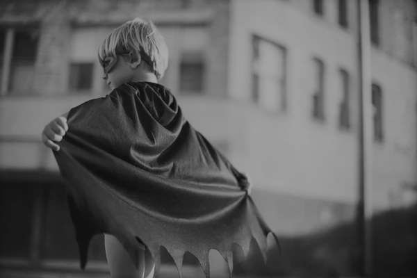A black and white picture of a young boy wearing superhero costume.